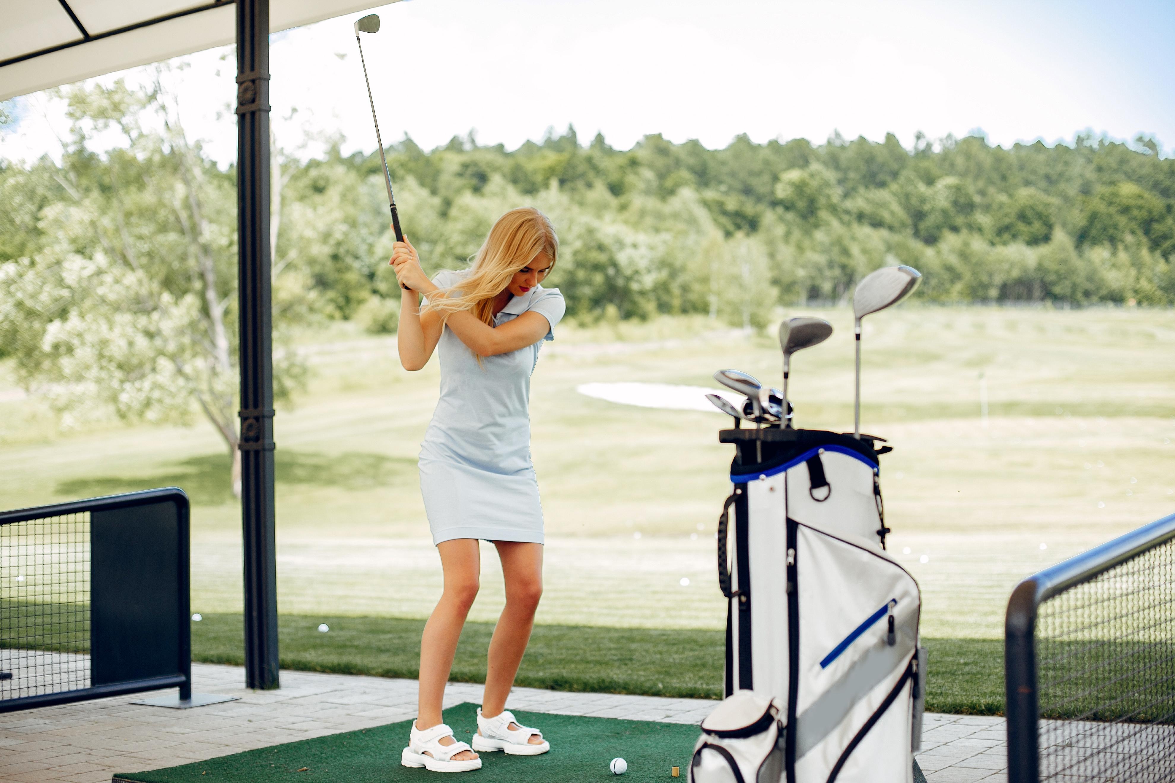 Vrouw slaat bal vanaf de afslagplaats op de golfbaan
