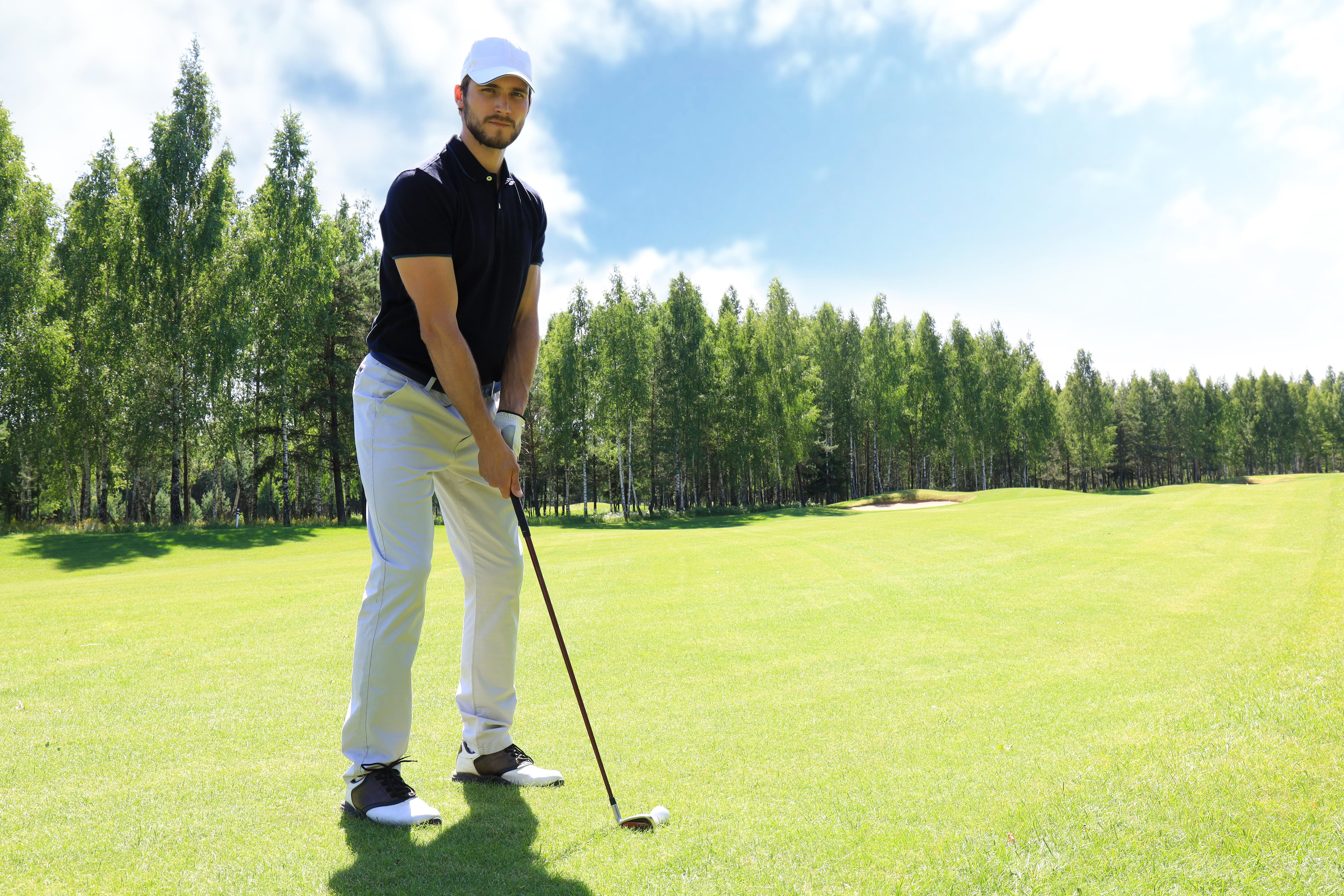 Een man met een golfpet en een polo aan staat met een golfclub op de golfbaan