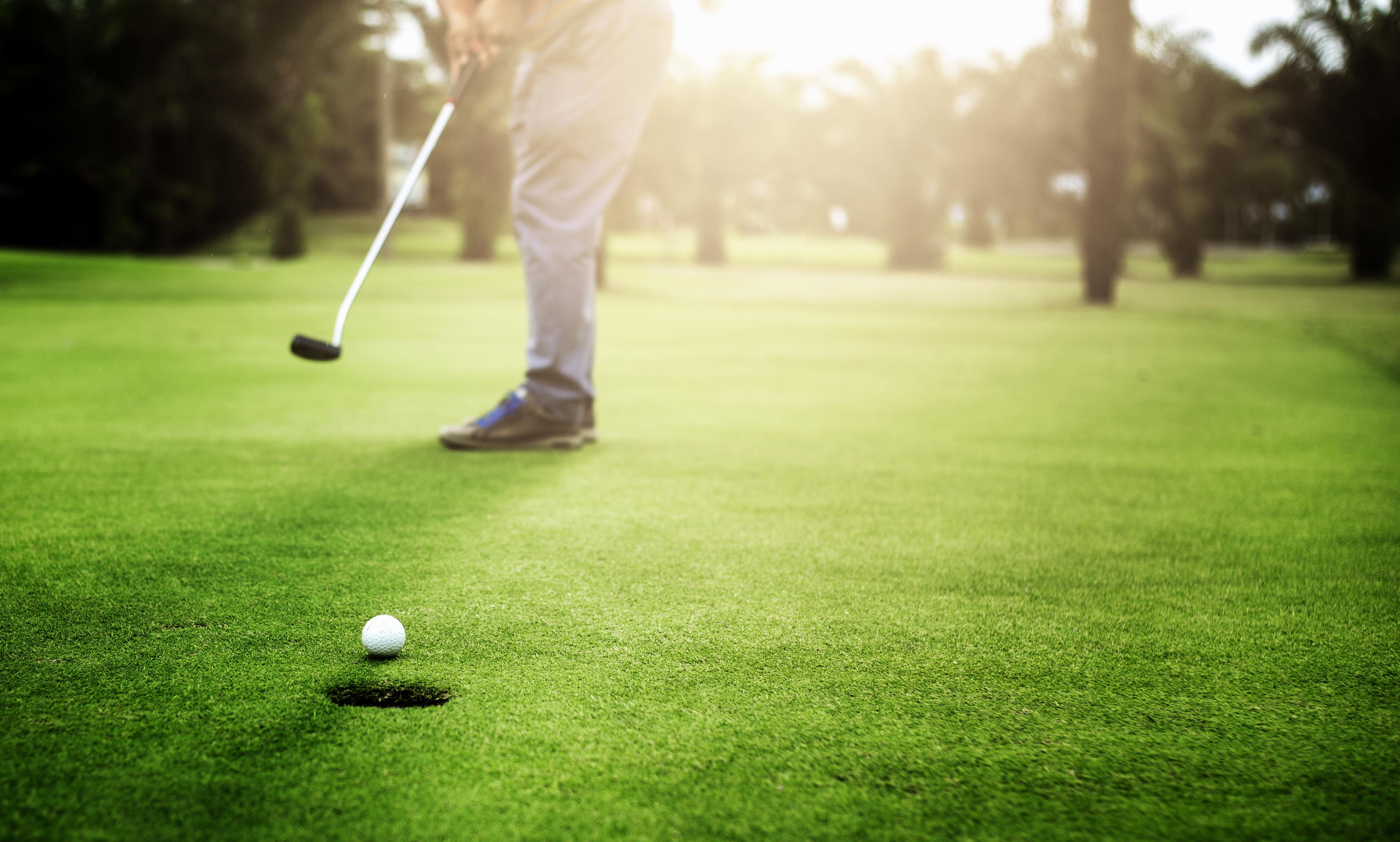 Een man slaat een golfbal richting de hole