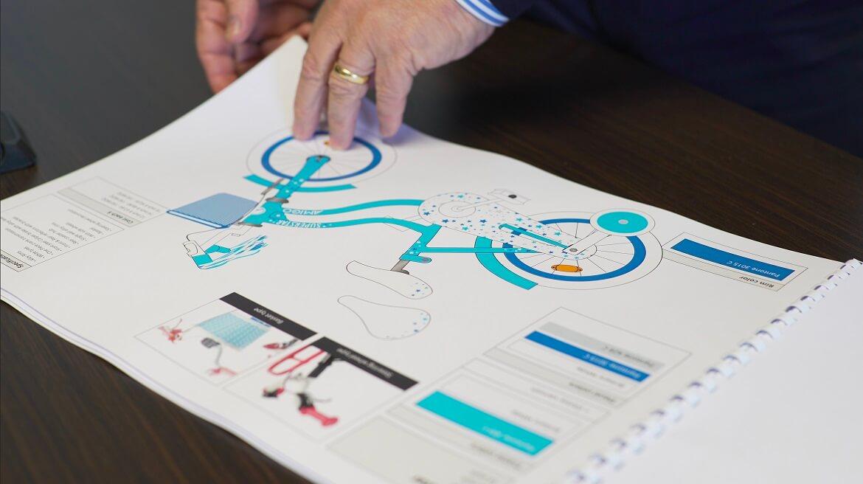 Een volledig uitgetekend ontwerp van een AMIGO kinderfiets wordt bekeken