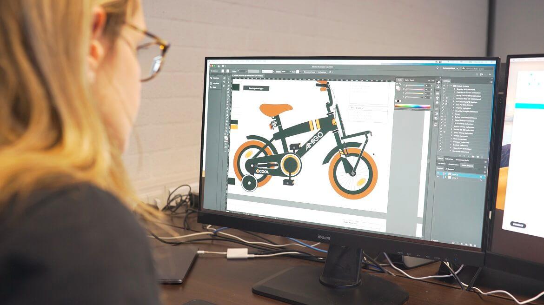 Designer ontwerpt een AMIGO kinderfiets op de computer