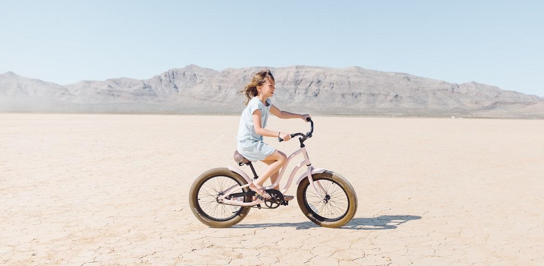 Meisje dat op een kinderfiets over een zandvlakte fietst