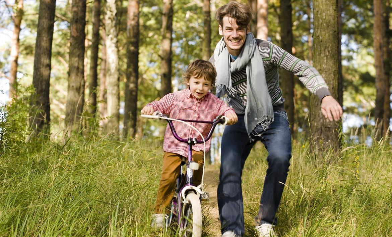 Vader geeft zoon op de fiets een zetje om hem te leren fietsen