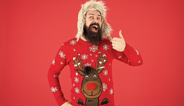 Man met een kersttrui aan steekt zijn duim op