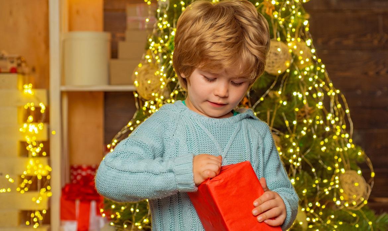 Kinderen kunnen niet van cadeaus afblijven, heeft onderzoek uitgewezen. Hier zie je een kind dat een cadeau open maakt.