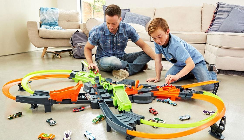 Vader en zoon spelen met auto's op een lanceerbaan