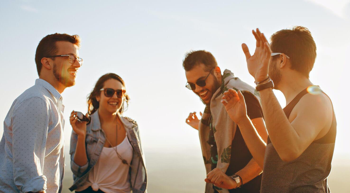 Vier lachende mensen met brillen en zonnebrillen op