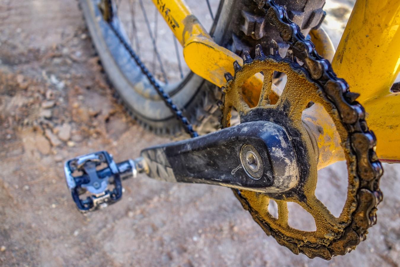 Vieze ketting en trapper, gele fiets