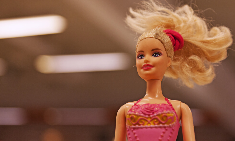 Barbiepop met blond haar en roze jurk