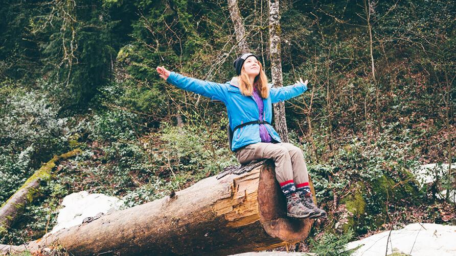 Meisje zit op een boomstam tijdens een hike