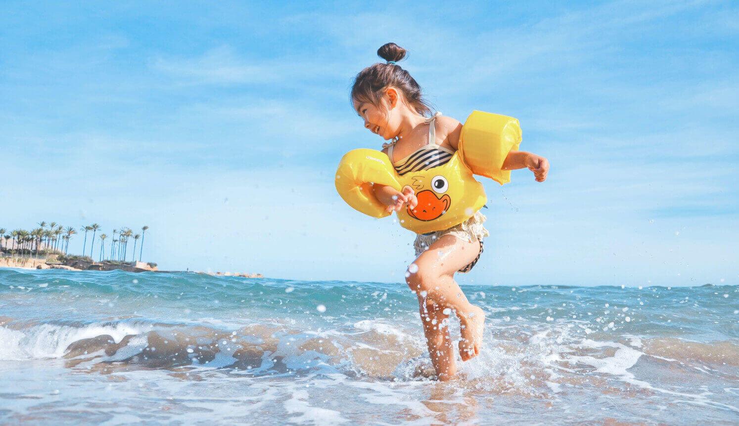 Kind met zwembandjes in de zee